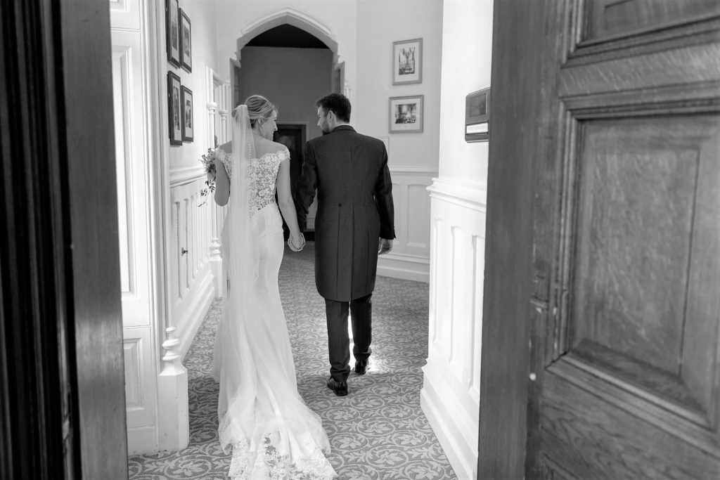 bride groom stroll corridor holding hands the elvetham hartley wintney hampshire oxfordshire wedding photographer