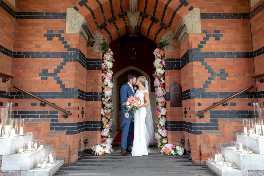 bride groom kiss under floral arch the elvetham hartley wintney hampshire oxfordshire wedding photography