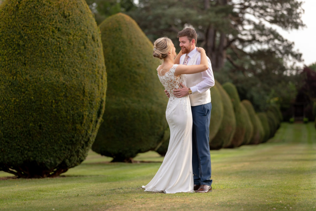 bride groom embrace on tree lined walk the elvetham gardens hartley wintney hampshire oxford wedding photographer
