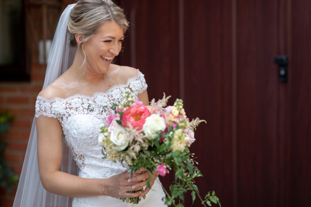29 laughing bride colourful flowers bouquet the elvetham hartley wintney hampshire oxfordshire wedding photographers