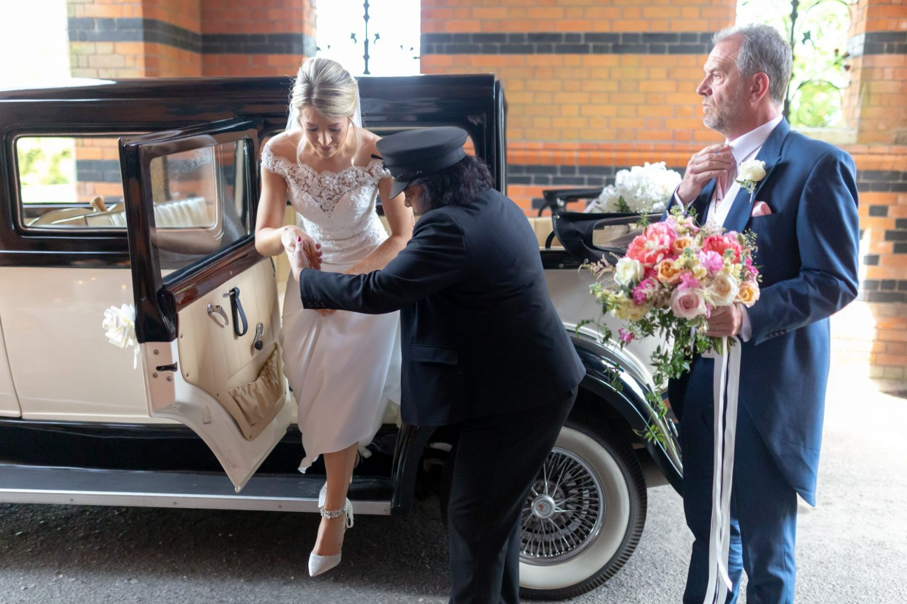 32 bride steps out bridal car fahter of bride holds bouquet the elvetham hartley wintney hampshire oxford wedding photographers
