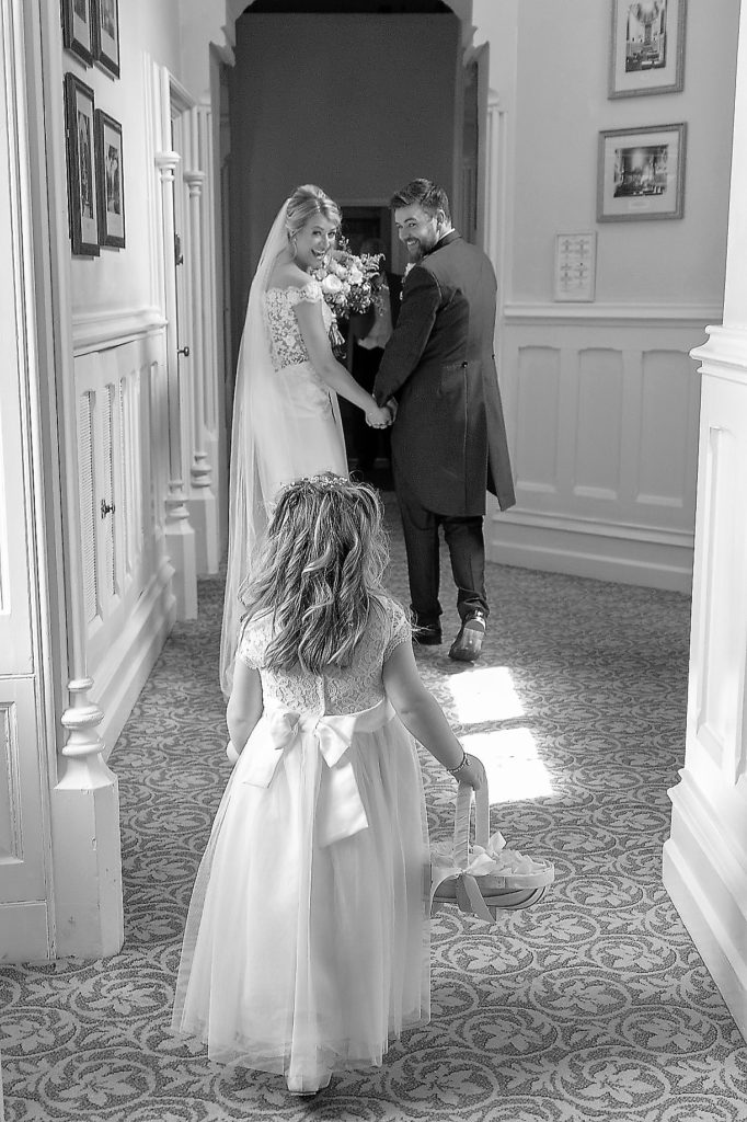 57 flower girl walks behind bride groom the elvetham venue hartley wintney hampshire oxford wedding photography