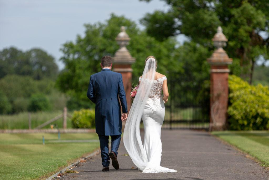 69 bride groom walk toward ornamental gates the elvetham hartley wintney hampshire oxford wedding photography