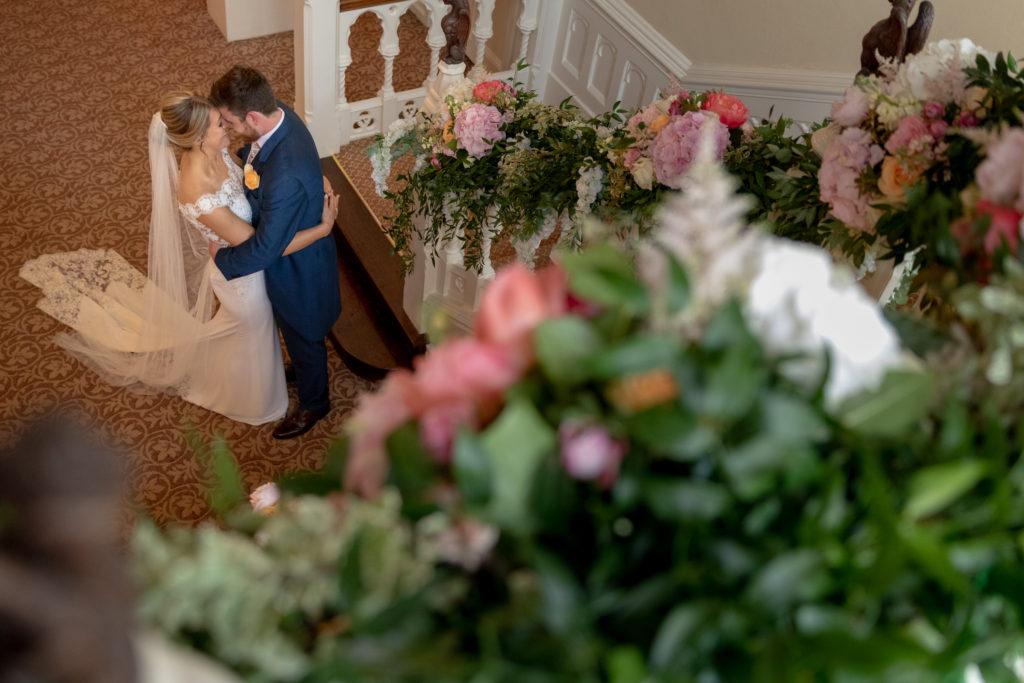 77 bride groom kiss below floral arrangement the elvetham venue hartley wintney hampshire oxfordshire wedding photographers
