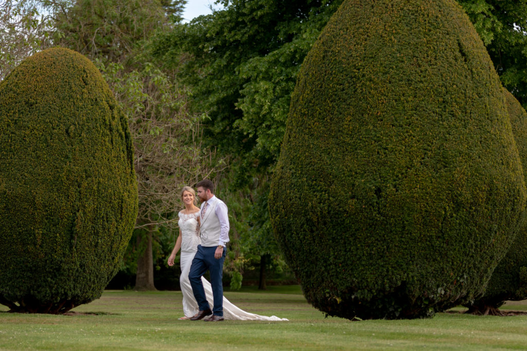 104 bride groom walk through topriary garden the elvetham hartley wintney hampshire oxford wedding photographers