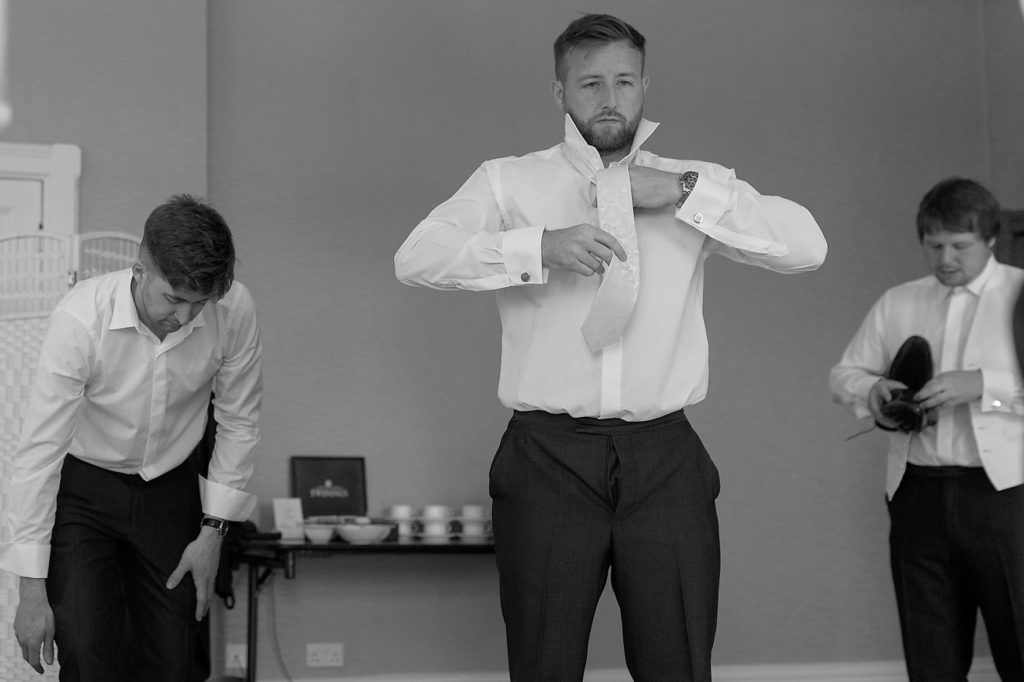 17 groomsmen adjust ties groom prep the elvetham hartley wintney hampshire oxfordshire wedding photographers