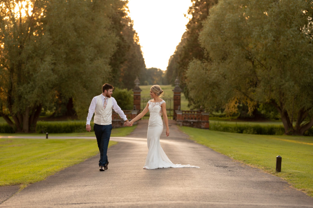 112 bride groom hold hands setting sun the elvetham gardens hartley wintney hampshire oxfordshire wedding photographer