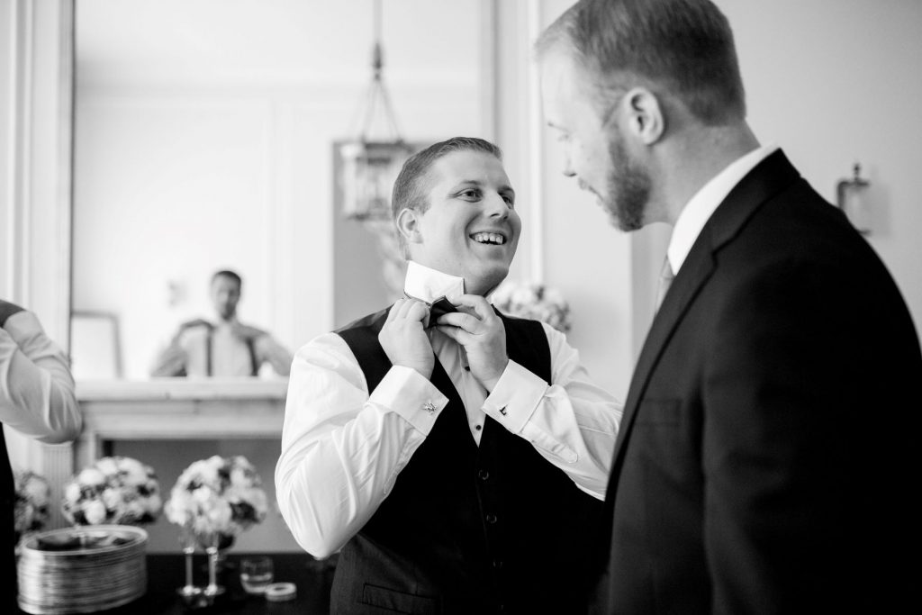 groom adjusts bow tie academy of medical sciences portland place london oxford wedding photographers