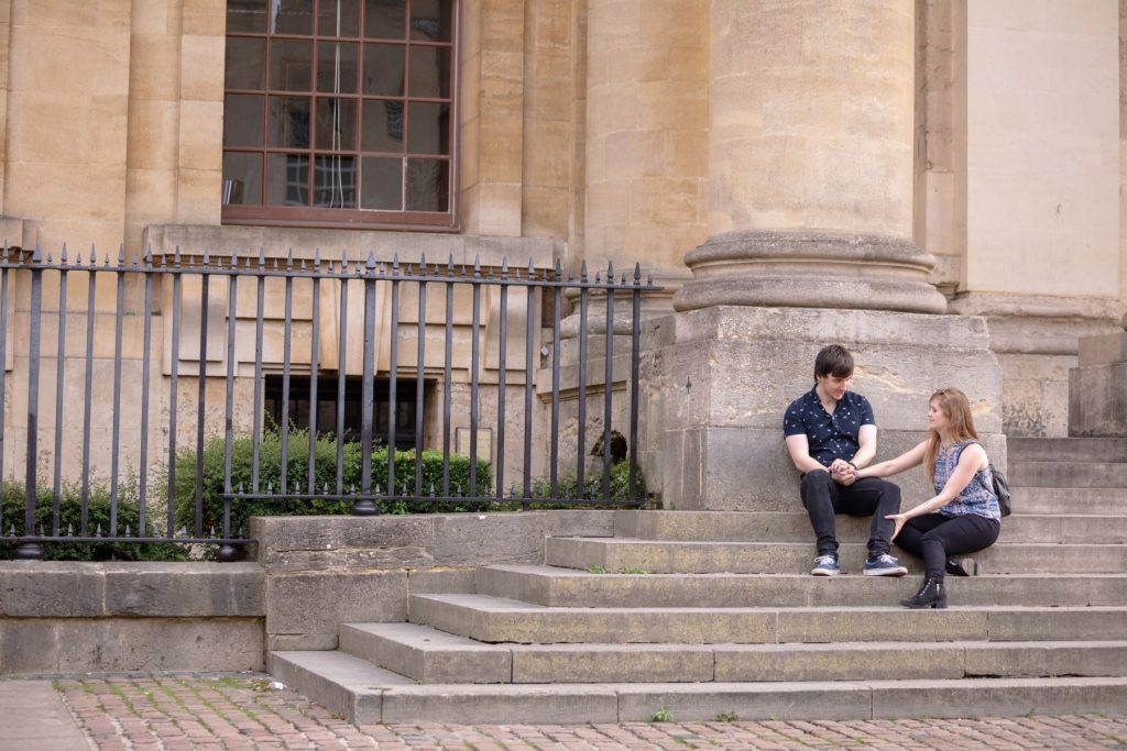 engaged couple talk oxford city centre steps engagement photo session oxfordshire wedding photographers