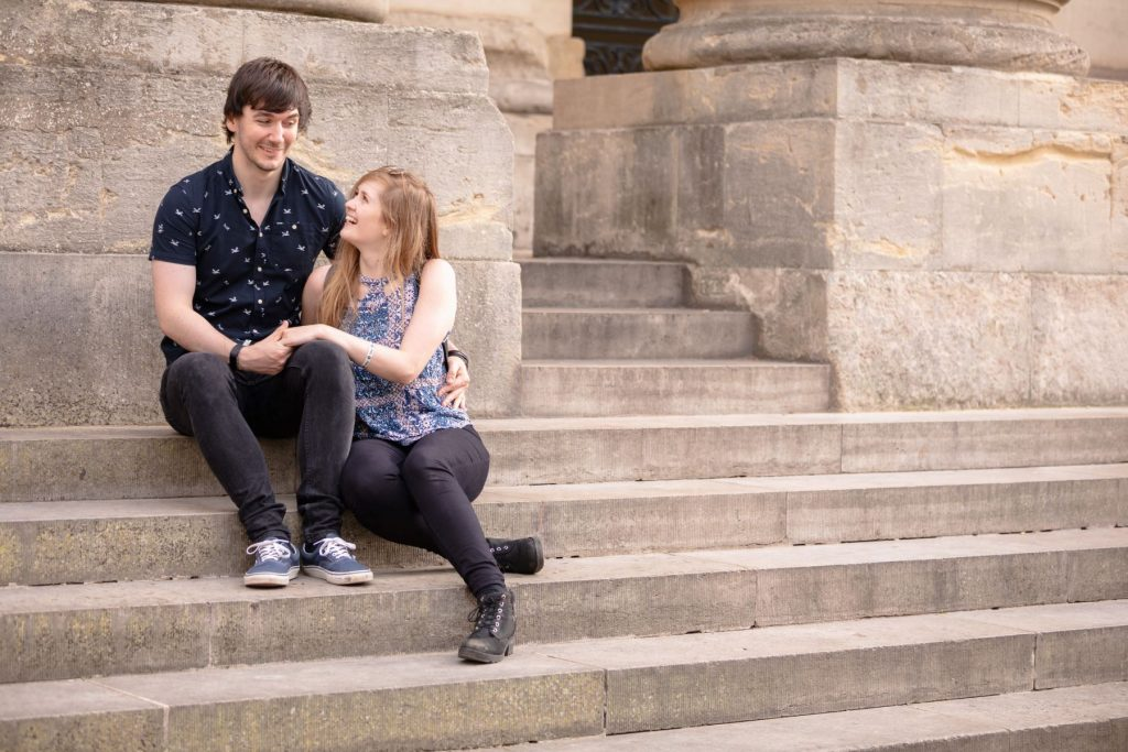 smiling couple on oxford city centre steps engagement photo shoot oxfordshire wedding photography