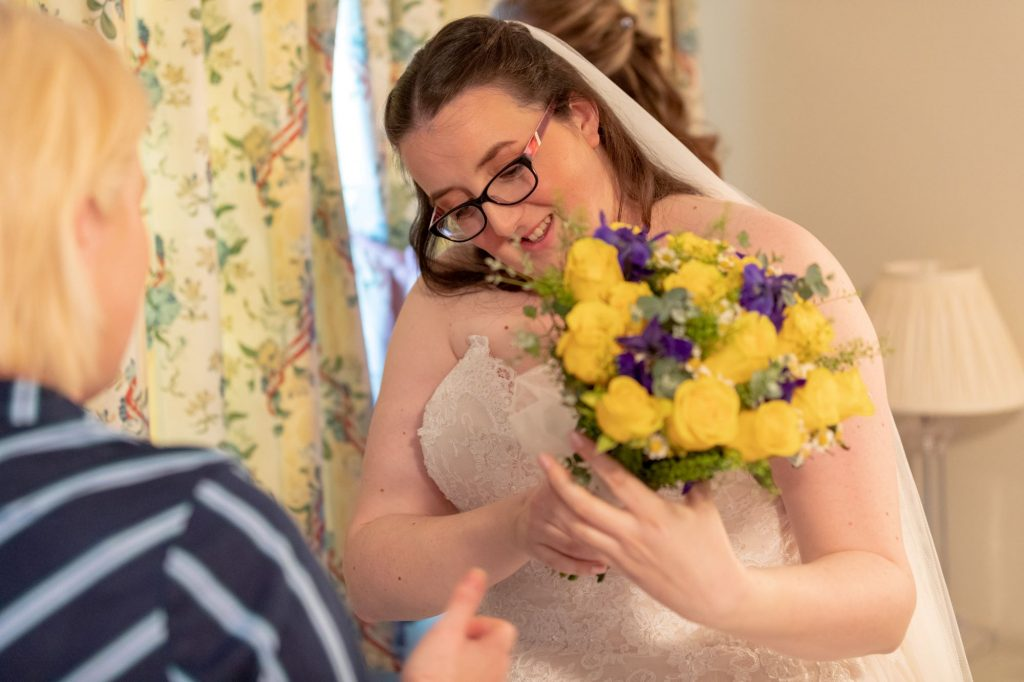 bride checks floral bouquet manor hill house bromsgrove worcestershire oxfordshire wedding photography