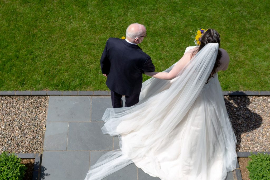 bride holds fathers arm before open air ceremony manor hill house bromsgrove worcestershire oxford wedding photographers