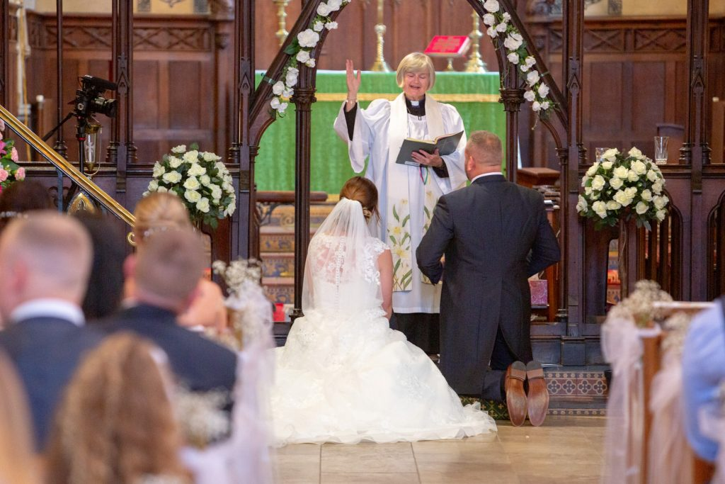 vicar blesses kneeling bride groom st marks church pensnett dudley west midlands oxfordshire wedding photographers