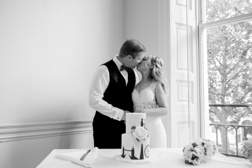 bride groom kiss cake cutting ceremony academy of medical sciences portland place london oxford wedding photographers