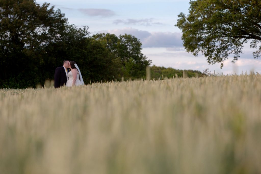 bride groom kiss in cornfield manor hill house bromsgrove worcestershire oxford wedding photographer