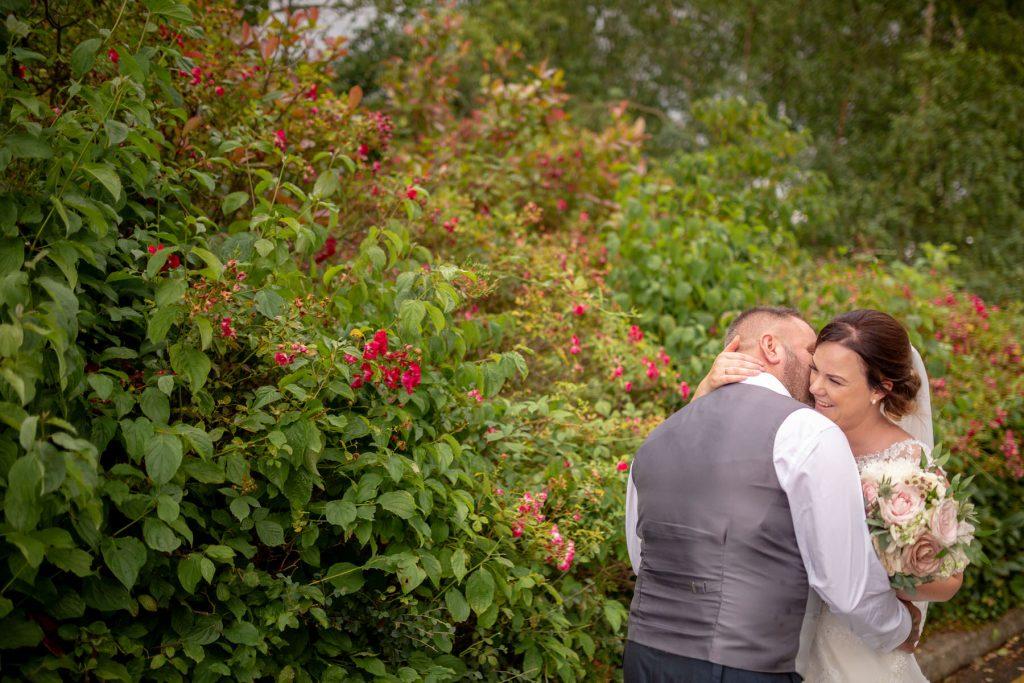 bride groom embrace near flower covered bush village hotel club gardens dudley birmingham oxford wedding photography