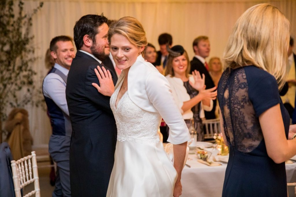 dinner guests applaud brides entrance marquee reception blenheim palace woodstock oxfordshire wedding photographers