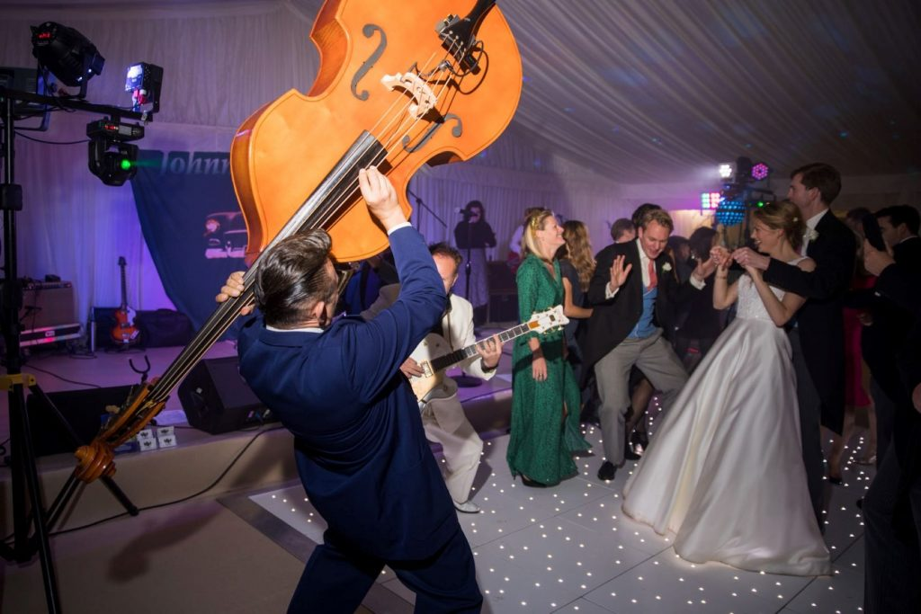 muscian holds double bass aloft marquee reception blenheim palace venue woodstock oxford wedding photographers