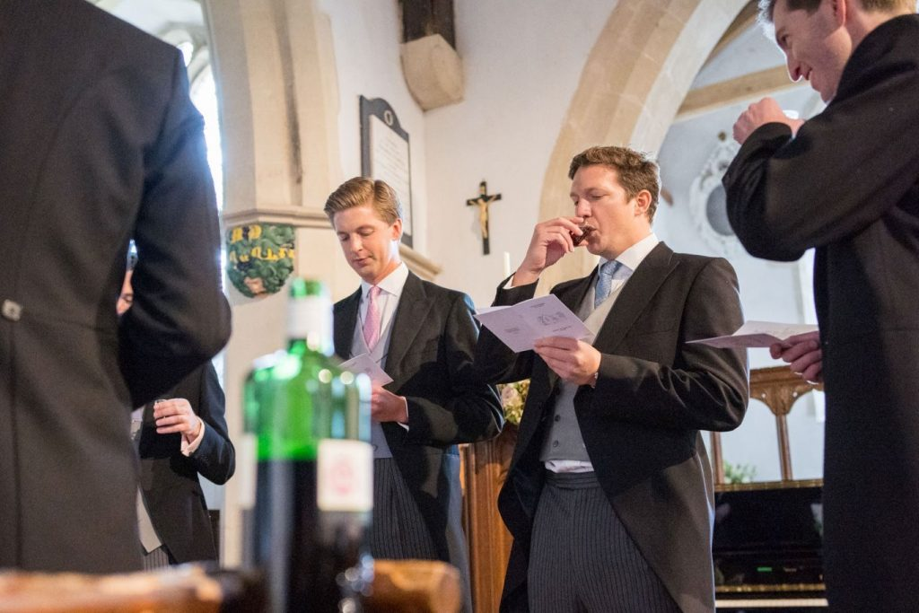 groomsen sip drinks before ceremony church of st michael aston tirrold oxfordshire oxford wedding photographer