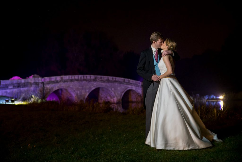 bride groom kiss beside floodlit bridge blenheim palace grounds woodstock oxfordshire wedding photography