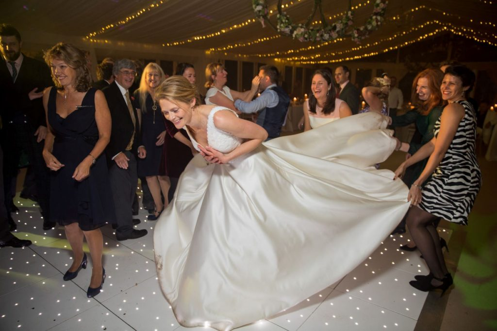guests lift brides train marquee reception blenheim palace venue woodstock oxfordshire wedding photographers
