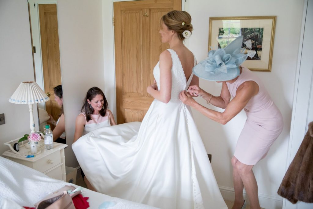 bridal preparation dress adjustment church of st michael ceremony aston tirrold oxfordshire wedding photographer