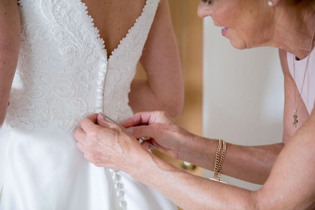 mother of bride fastens dress buttons church of st michael ceremony aston tirrold oxfordshire oxford wedding photographer