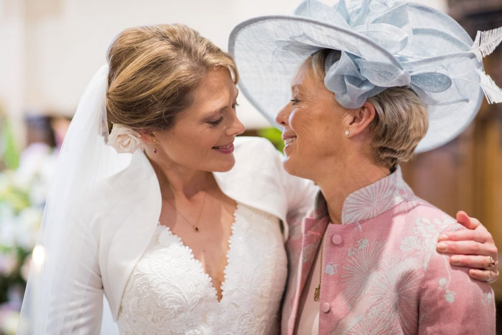bride hugs mother church of st michael aston tirrold ceremony oxfordshire wedding photography