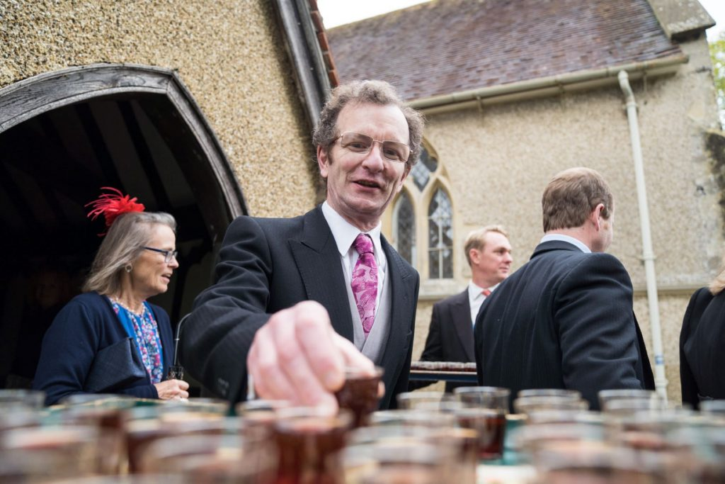 guest takes shot glass church of st michael churchyard aston tirrold oxfordshire oxford wedding photography