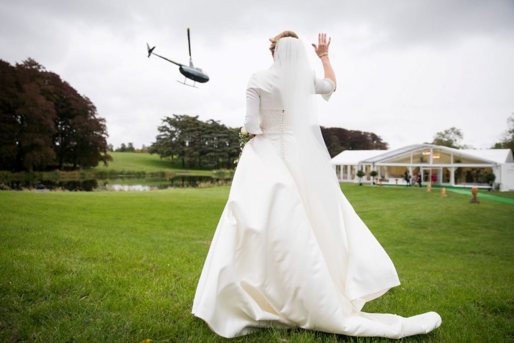 bride waves off helicoper from blenheim palace marquee woodstock oxfordshire wedding photographer