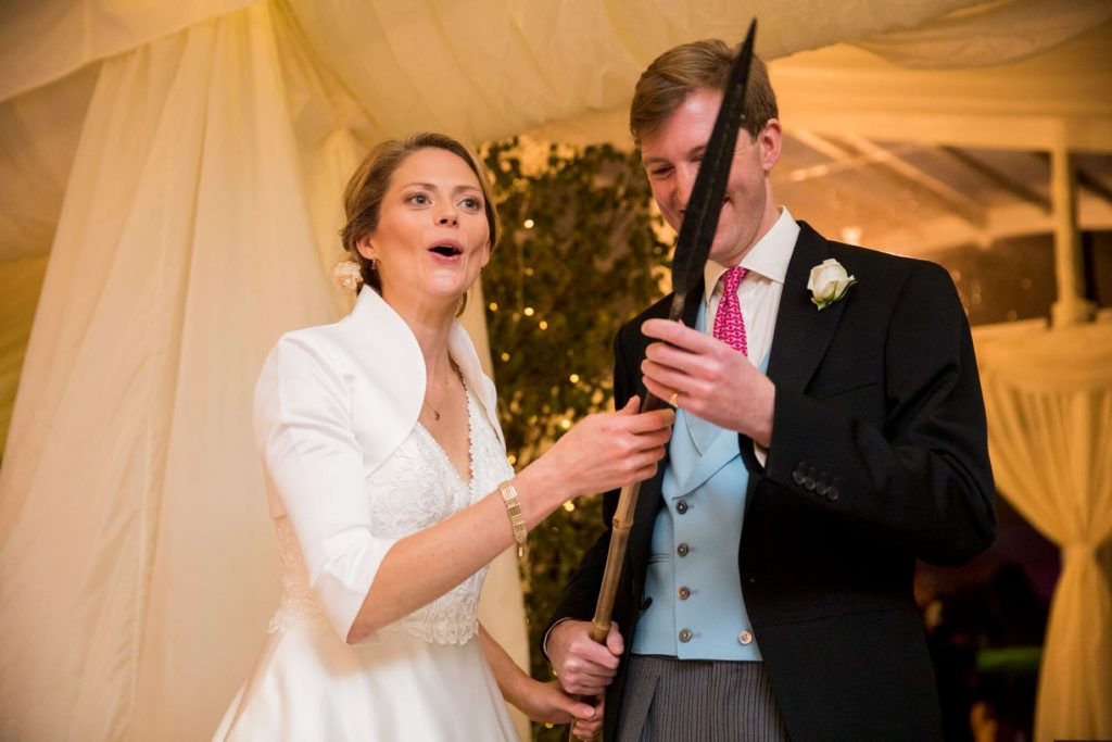 bride groom hold cake cutting spear blenheim palace woodstock oxfordshire oxford wedding photographers