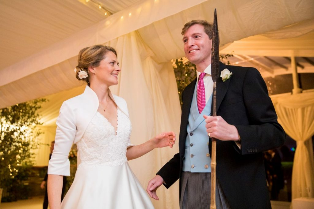 smiling bride groom with cake cutting spear marquee reception blenheim palace woodstock oxfordshire oxford wedding photography
