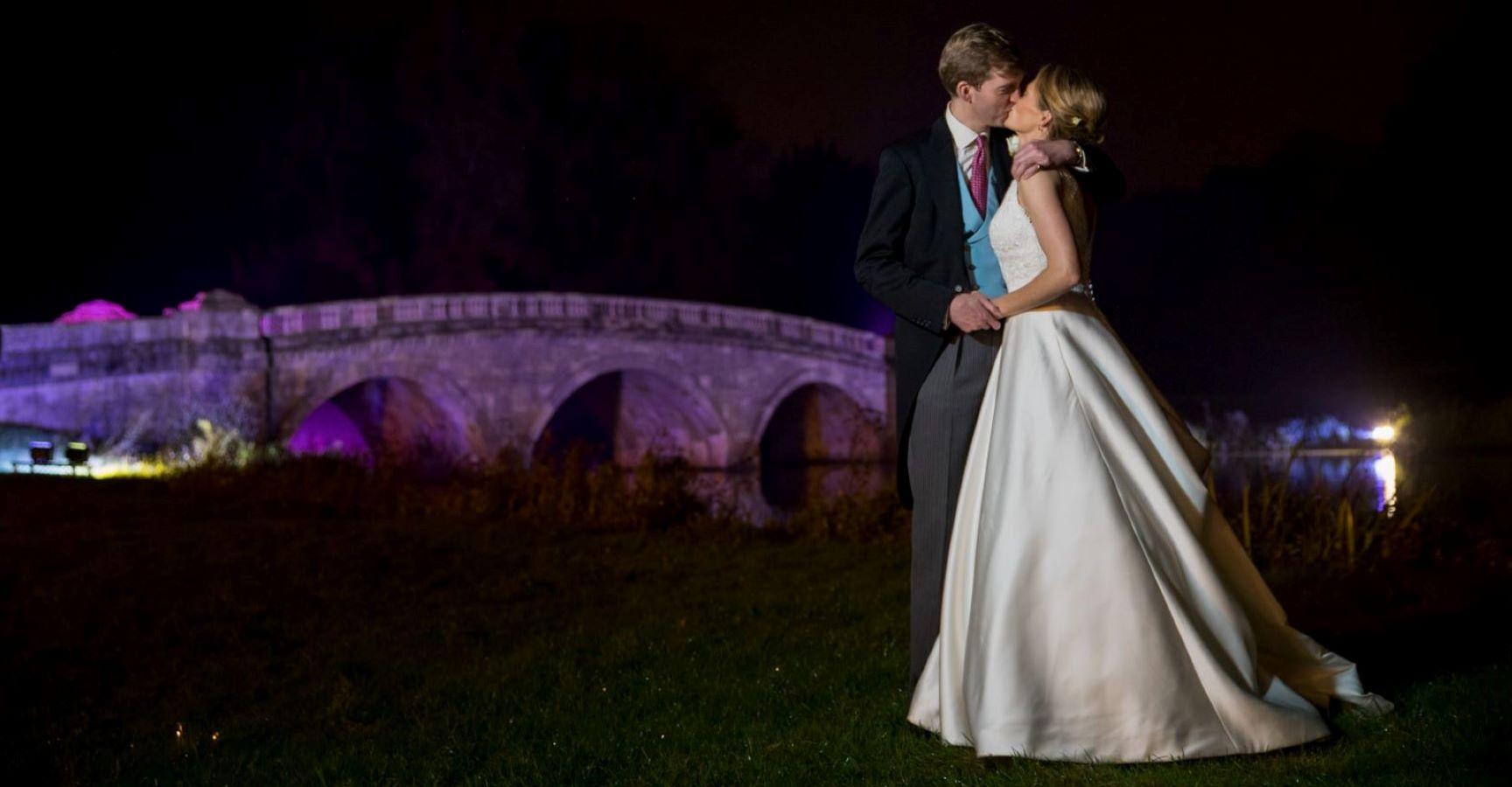 groom bride kiss beside floodlit bridge blenheim palace grounds woodstock oxfordshire wedding photography