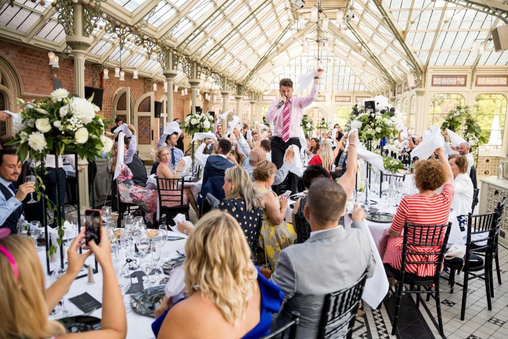 guests wave napkins entertainer sings kilworth house hotel orangery north kilworth leicestershire oxfordshire wedding photography