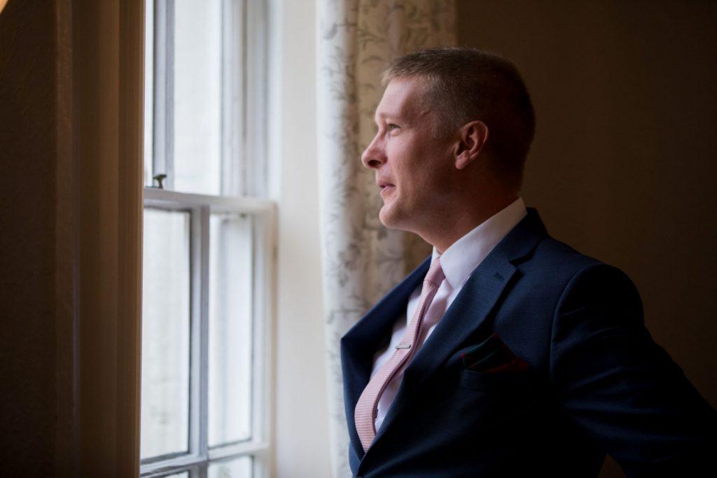 groom gazes registry office window roysse court abingdon oxford wedding photographers