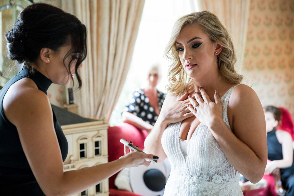 bridesmaid helps bride chech hairstyling bridal prep kilworth house hotel north kilworth leicestershire oxford wedding photographer