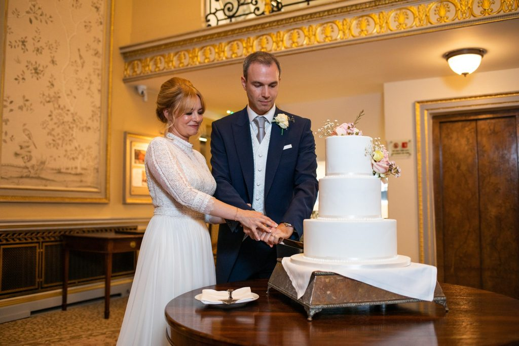 bride groom cut cake lansdown club mayfair london oxford wedding photographers