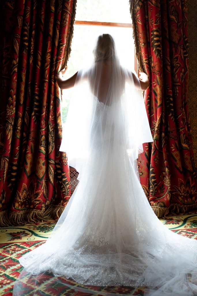 brides pushes curtains apart kilworth house hotel north kilworth leicestershire oxford wedding photographer