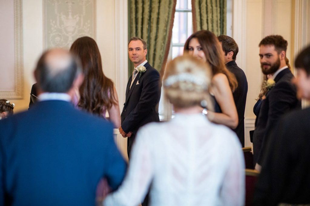 groom turns to greet bride lansdowne club marriage ceremony mayfair london oxfordshire wedding photographer