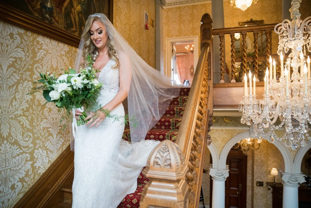 bride decends staircase holding bouquet kilworth house hotel north kilworth leicestershire oxfordshire wedding photographer
