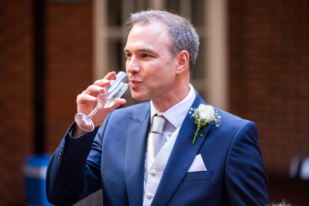 groom sips champagne lansdowne club reception mayfair london oxfordshire wedding photography