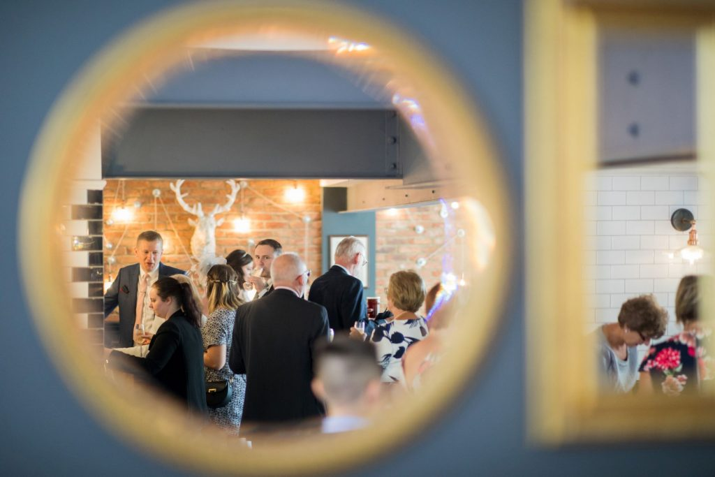 mirror reflects guests drinks reception broad face pub abingdon oxford wedding photography