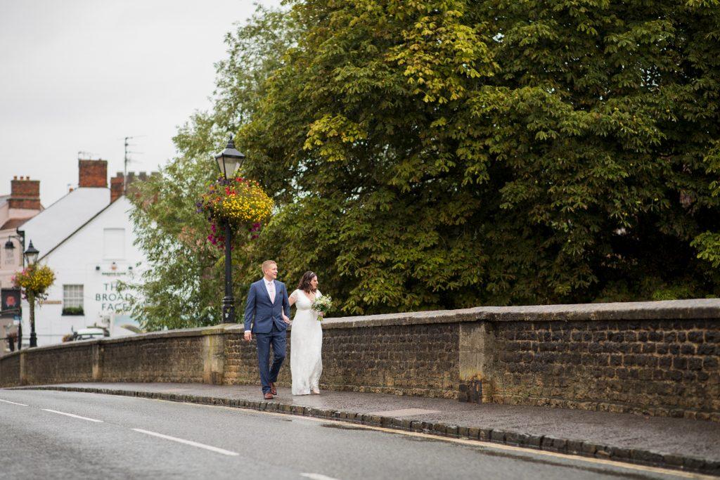 groom walks bride across bridge registry office ceremony roysse court abingdon oxfordshire wedding photographers