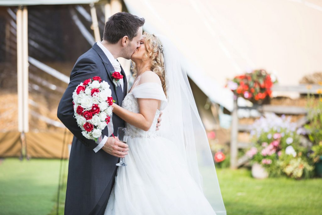 bride holding bouquet kisses groom wroxeter hotel shrewsbury shropshire oxford wedding photographers
