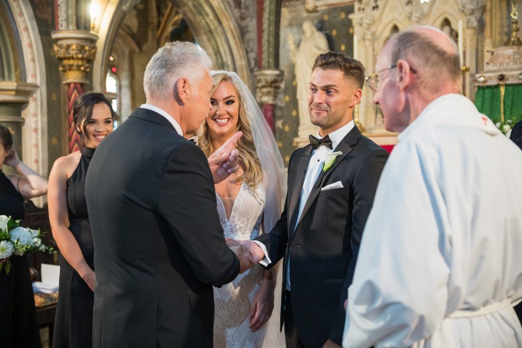 father of bride shakes groom hand st marys catholic church marriage ceremony husbands bosworth leicestershire oxford wedding photography