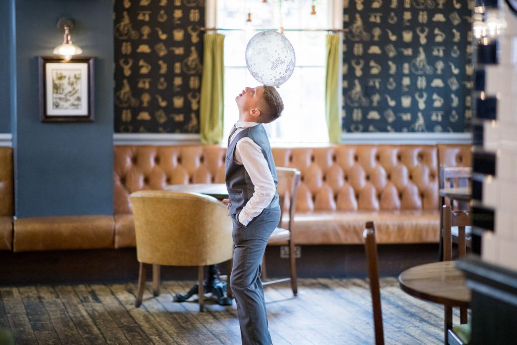 a young guest balances balloon broad face pub reception abingdon oxfordshire wedding photographer