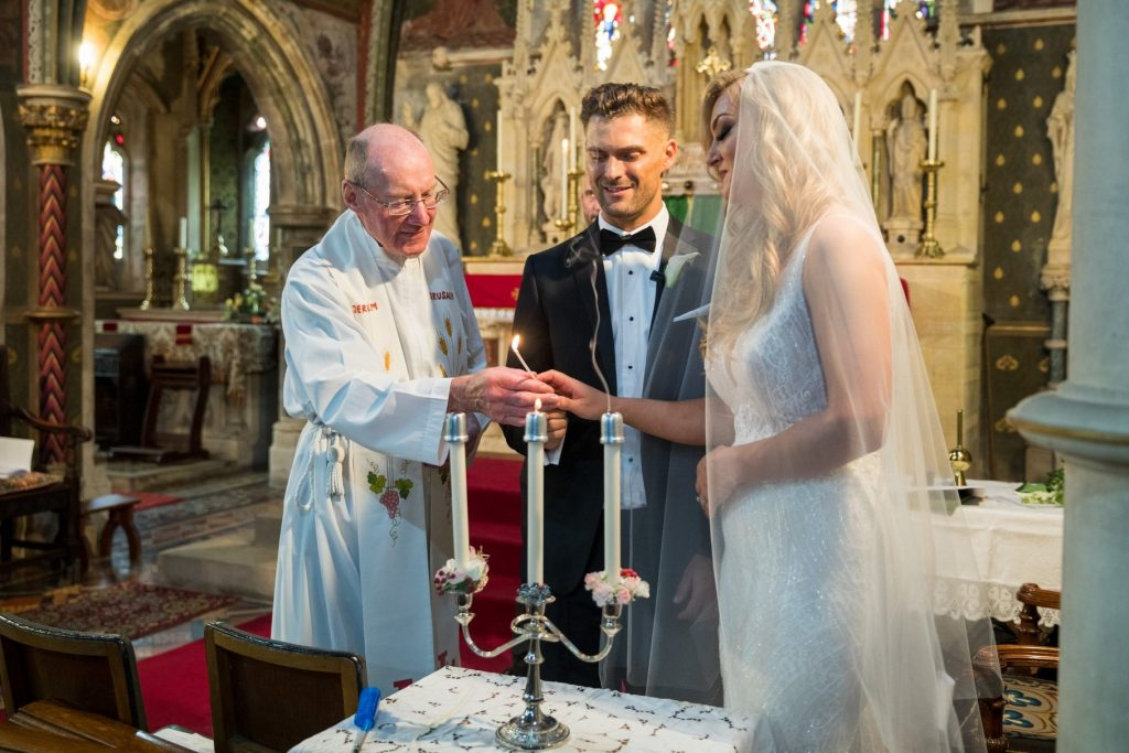 priest assists bride groom lighting candles st marys catholic church husbands bosworth leicestershire oxford wedding photography