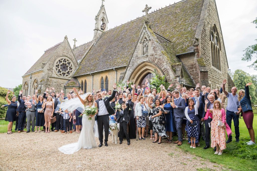bride groom guests wave outside st marys catholic church husbands bosworth leicestershire oxfordshire wedding photographer