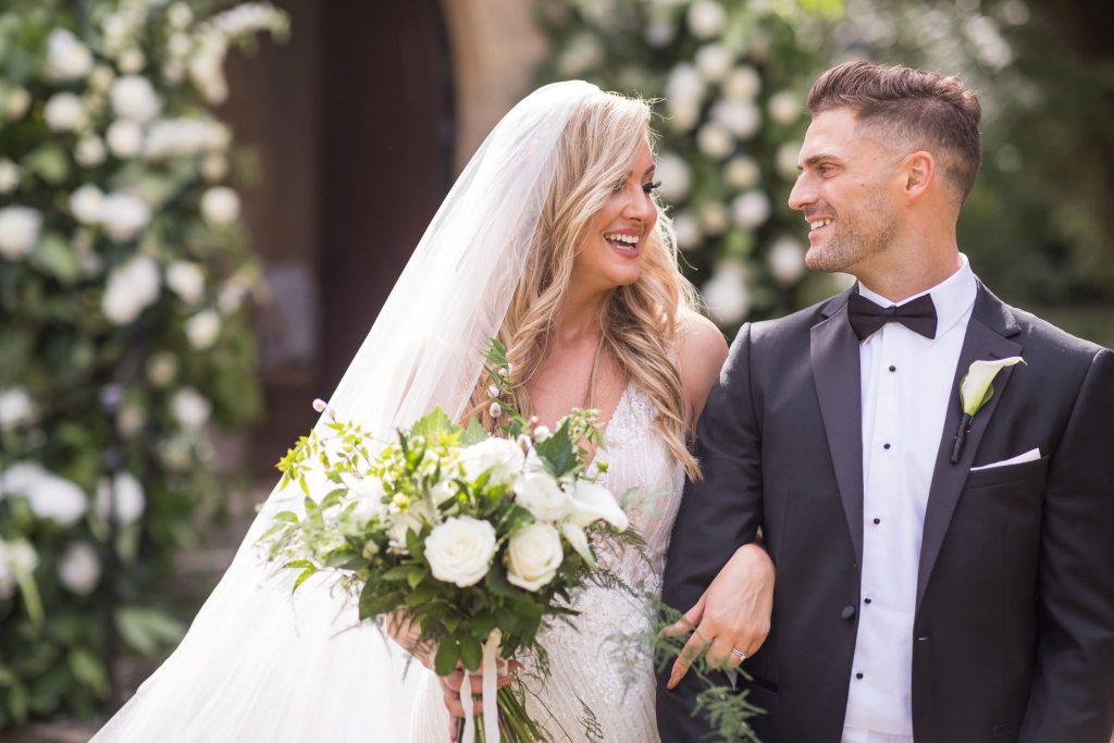 smiling bride groom arm in arm st marys catholic churchyard husbands bosworth leicestershire oxfordshire wedding photography