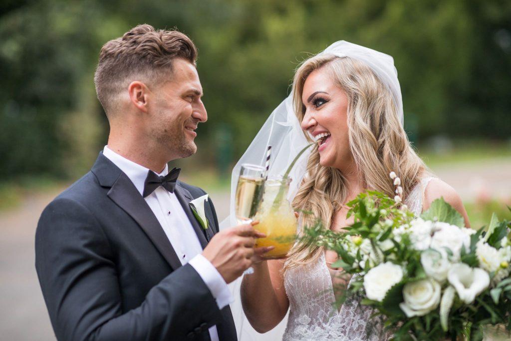 smiling bride groom raise glasses kilworth house hotel grounds north kilworth leicestershire oxfordshire wedding photographers